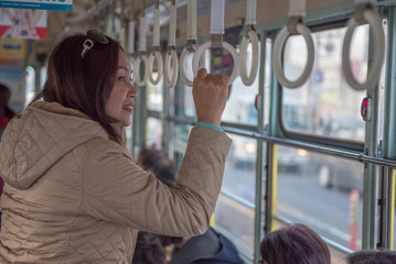 Safety travel trip, young passenger woman hand holding Handle on the train or on the bus for safety.