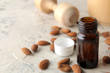 natural cosmetic almond oil in a glass jar and fresh almond nuts on a light concrete background. close-up