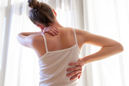 Young woman suffering from neck pain and backache, stretching the muscles.