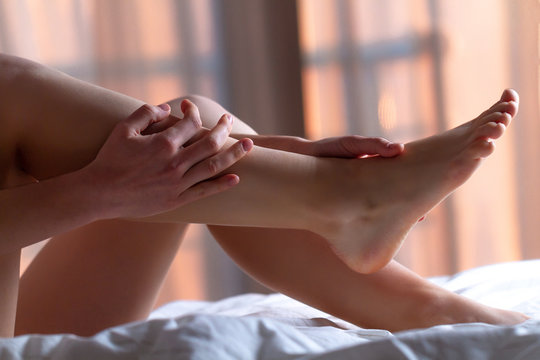 Young woman doing a relaxing foot massage at home on the bed after a long, hard working day. Manual therapy. Treatment pain, fatigue and discomfort legs