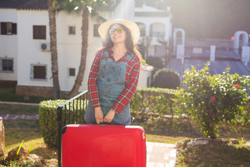 Travel, tourism and people concept - happy young woman in hat carry a huge red suitcase and smile over the nature background