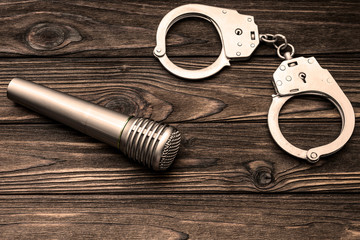 handcuffs, microphone on wooden background. violation of copyright law.