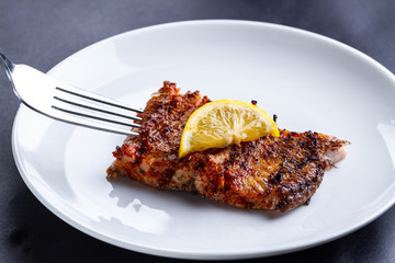 Fresh, grilled salmon fillet with a slice of juicy lemon on a white plate