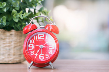 Red clock on wooden table. Starting the new day.