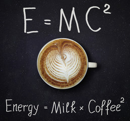 The cup of black coffee with milk and two funny formulas. Night sky background.