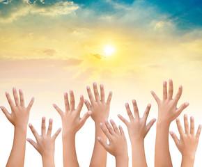 kids Raising hands up together on sunset sky background