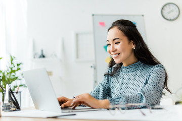 beautiful smiling asian businesswoman sitting at desk and using laptop in office
