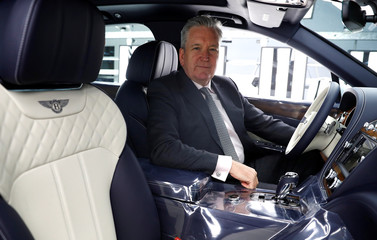 Adrian Hallmark, CEO of Bentley Motors, poses for a photograph inside one of his company's cars on the production line of their factory in Crewe