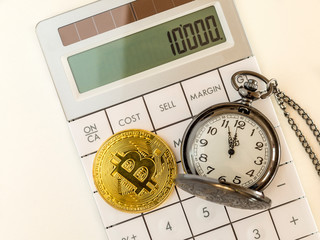 Golden bitcoin and pocket watch on calculator