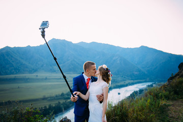 Beautiful young wedding couple making selfie on the background of mountains and river