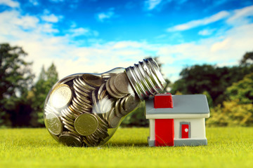 Coins inside the light bulb and miniature house on the grass. Green eco renewable energy concept. Electricity prices, energy saving in the household.