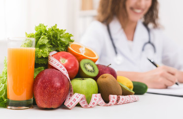Female nutritionist doctor writing vegetable diet plan