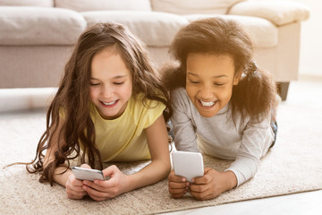 Little friends playing on smartphones, lying on floor