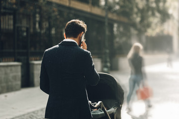 businessman parent outside with stroller on the street dressed in suit, looking elegant and fashion talking at the phone