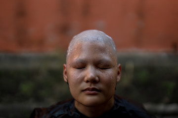 A devotee is pictured after her hair and eyebrows have been shaved during a mass female Buddhist novice monk ordination ceremony at Songdhammakalyani Monastery, Nakhon Pathom province