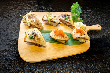 Grilled fillet sushi with fish roe on a wooden dish