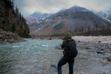 Professional Photographer is taking the picture of the river in Sonamarg, Kashmir India. Travel and tourism concept.