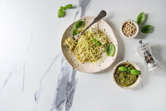 Classic italian spaghetti pasta with pesto sauce, pine nuts, olive oil and fresh basil. Served in ceramic plate with fork and ingredients above over white marble background. Flat lay, space