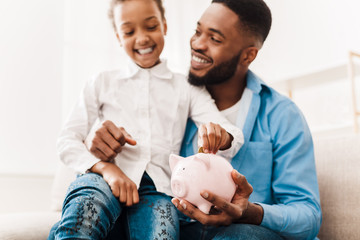 Girl and father putting coin into piggy bank