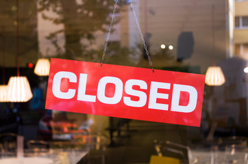 Closed sign on the glass door of the shop