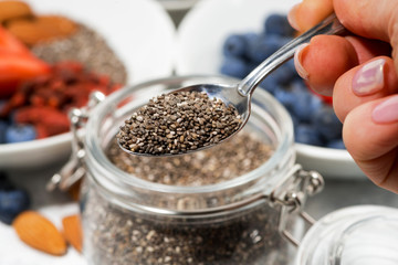 chia seeds in a jar, berries and nuts for a healthy breakfast, selective focus