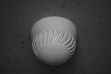 smoke detector on a gray wall in a new building, fire safety. protection of the apartment or house from fire and smoke. take care