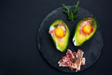 tasty baked avocado with an egg on a black background