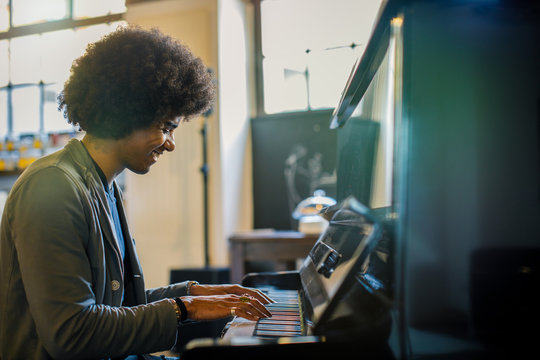 Afro american man playing piano at restaurant lounge