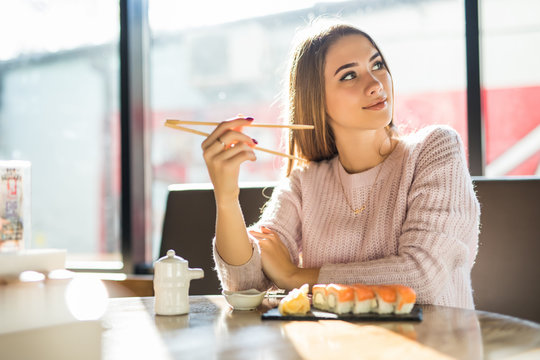 Young beautiful blond girl eating sushi of a Japanese restaurant
