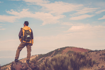 Man hiking at sunset mountains with light backpack Travel Lifestyle wanderlust adventure concept summer vacations outdoor alone into the wild  - blue background sky and valley around
