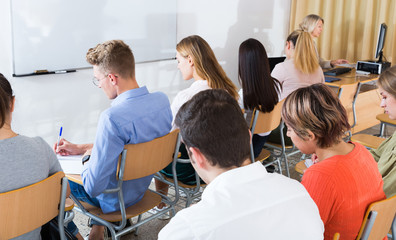 Students writing examination with female professor
