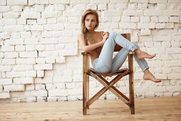 Amazing beautiful blond girl posing for photo in loft studio