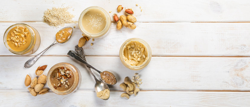 Selection of nut butters - peanut, cashew, almond and sesame seeds, copy space