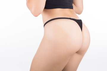 Female cropped buttocks in black string panties, isolated on white.