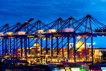Container Cargo freight ship with working crane bridge in shipyard at dusk