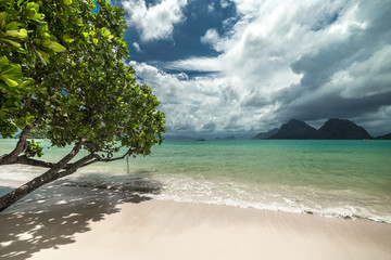 Tropical beach with trees, clouds sky, turquoise water and white sand in El Nido, Philippines