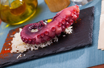 Delicious cooked octopus tentacles on a chopping board