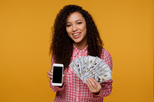 Portrait of an excited young african woman holding bunch of money banknotes and looking at mobile phone isolated over yellow background