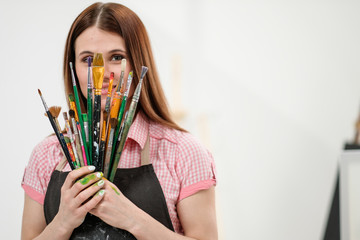 Young woman artist with brushes and paints in a white studio.