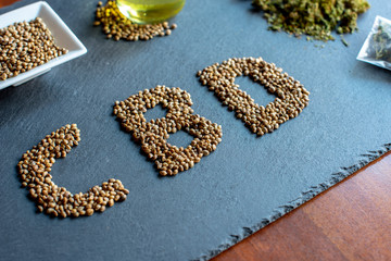abbreviation of the active ingredient cbd on a slate with medical marijuana sprouts, hemp seeds, essential oil