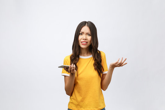 Portrait of a furious asian woman talking on mobile phone isolated over white background
