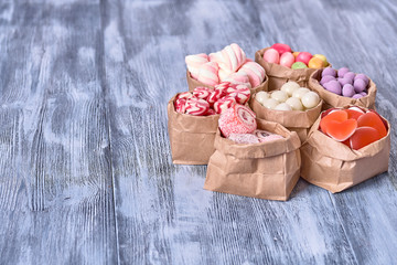 Colored candy in paper bags on wooden background