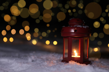 Lantern with burning candle on snow against blurred background, space for text. Winter decor