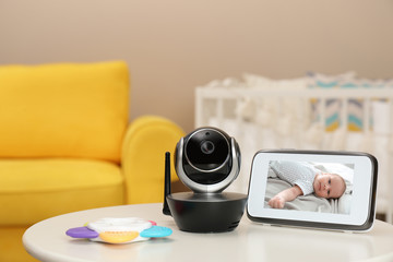 Modern security CCTV camera and monitor with baby's image on table. Space for text
