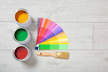 Flat lay composition with cans of paint, color palette samples and brush on wooden background. Space for text