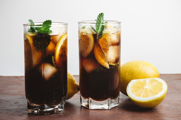 Cuba Libre cocktail with rum, cola, mint, lemon and ice in the glass on a brown table and white background
