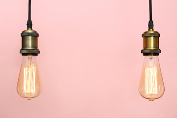 Pendant lamps with light bulbs on color background, space for text