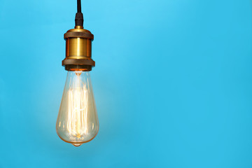 Pendant lamp with light bulb on color background, space for text