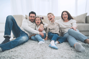 happy family sitting on the carpet in the living room.