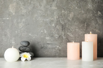Spa composition with burning candles on table, space for text